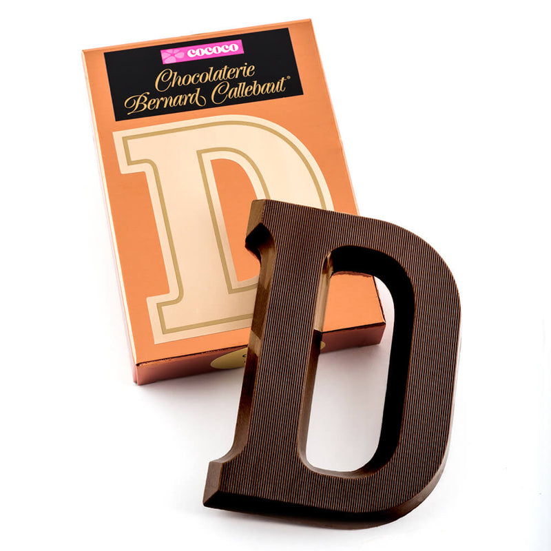 Dark chocolate letter D on top of it's Chocolaterie Bernard Callebaut®  box