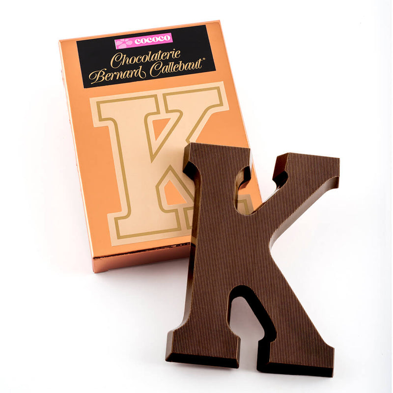 Dark chocolate letter K on top of it's Chocolaterie Bernard Callebaut®  box