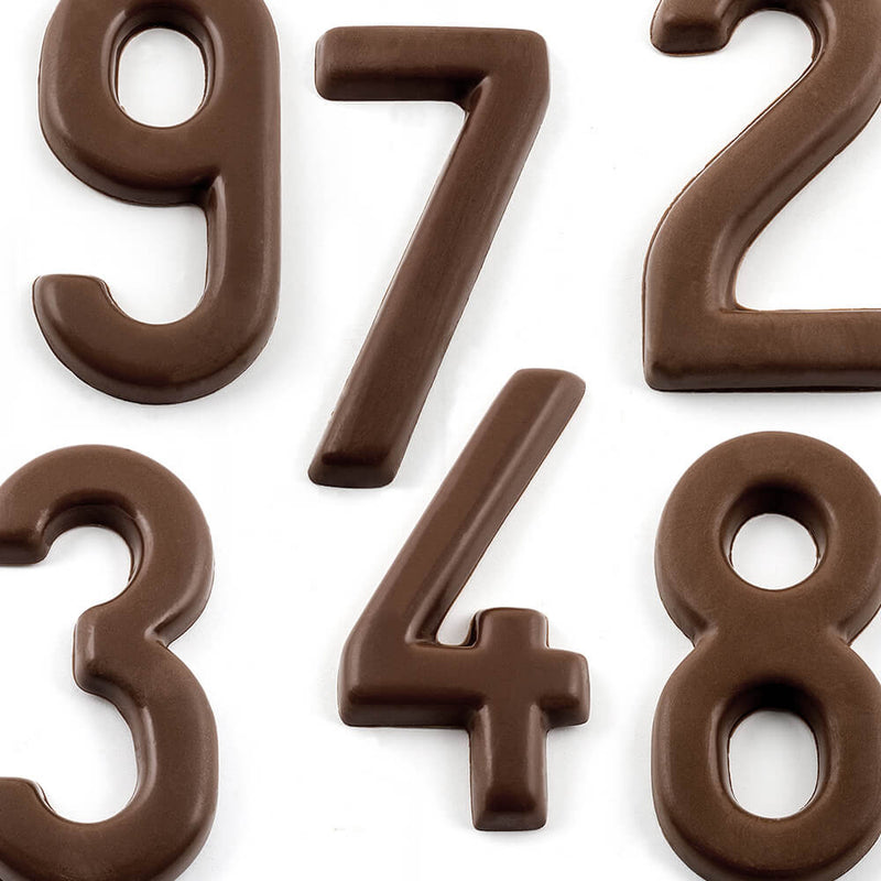 Top view of dark chocolate numbers 9, 7, 4, 2, 8, and 3