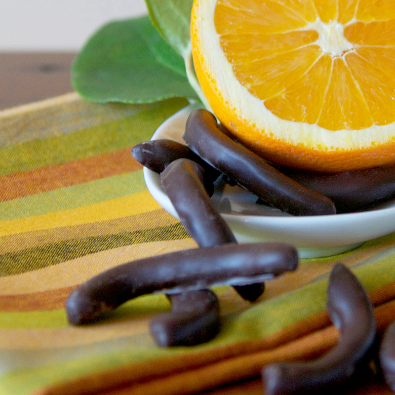 Dark chocolate coated orange peel with 1/2 orange on a green striped tablecloth