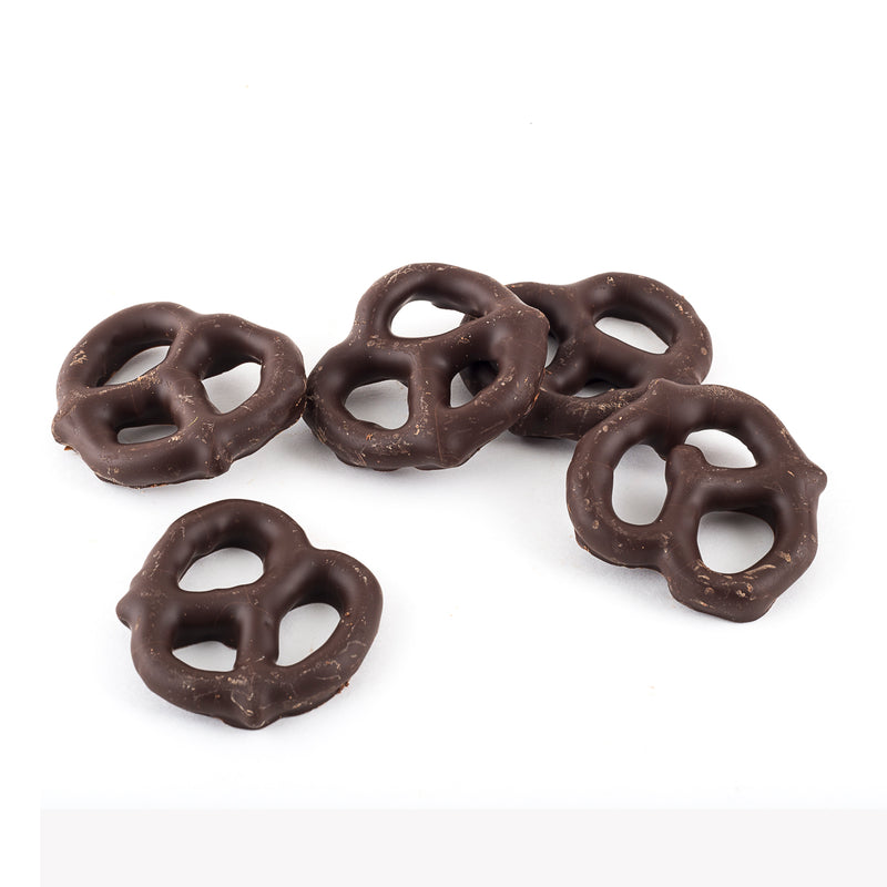 Five dark chocolate coated pretzels on a white background