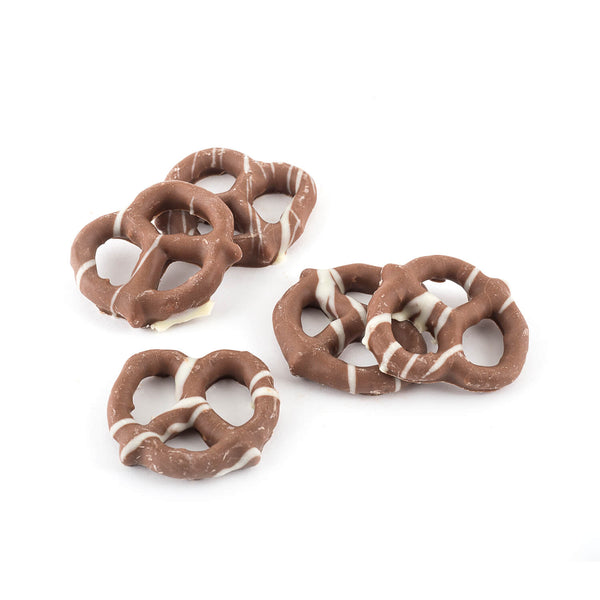 Close up milk chocolate coated pretzels that are dressed with lines of white chocolate