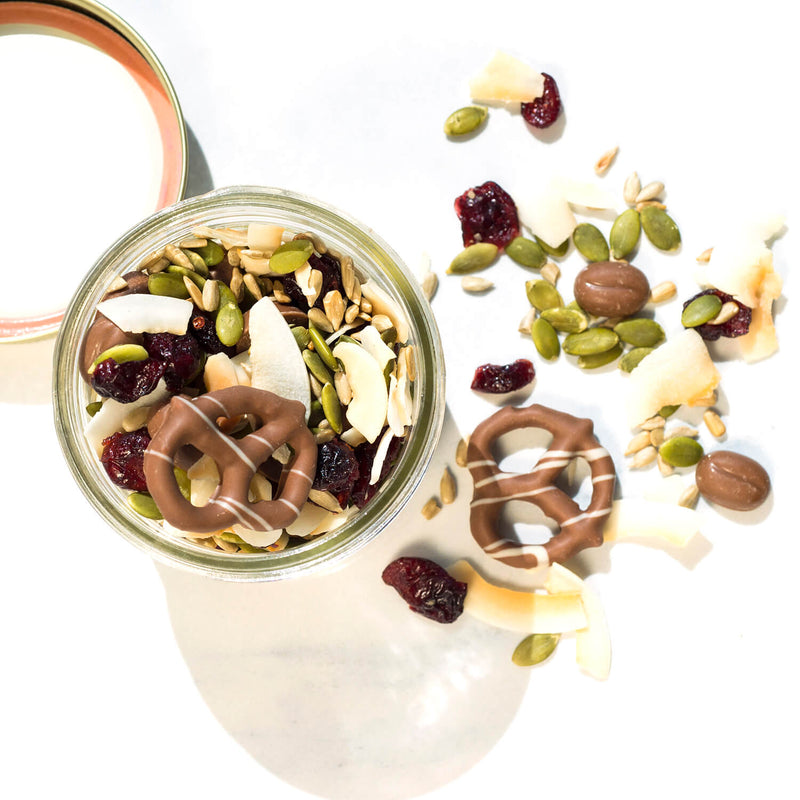 Top view of jar full of trail mix made up of milk chocolate pretzels and morsels along with seeds and coconut flakes