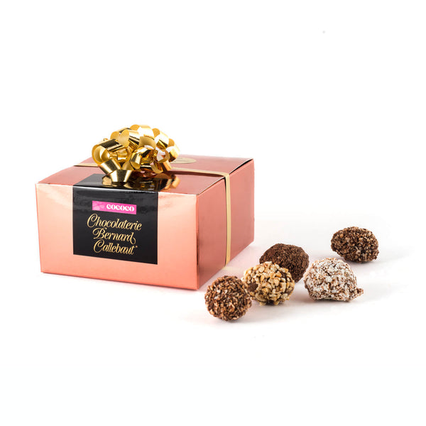 A Chocolaterie Bernard Callebaut® copper box with five truffles next to box