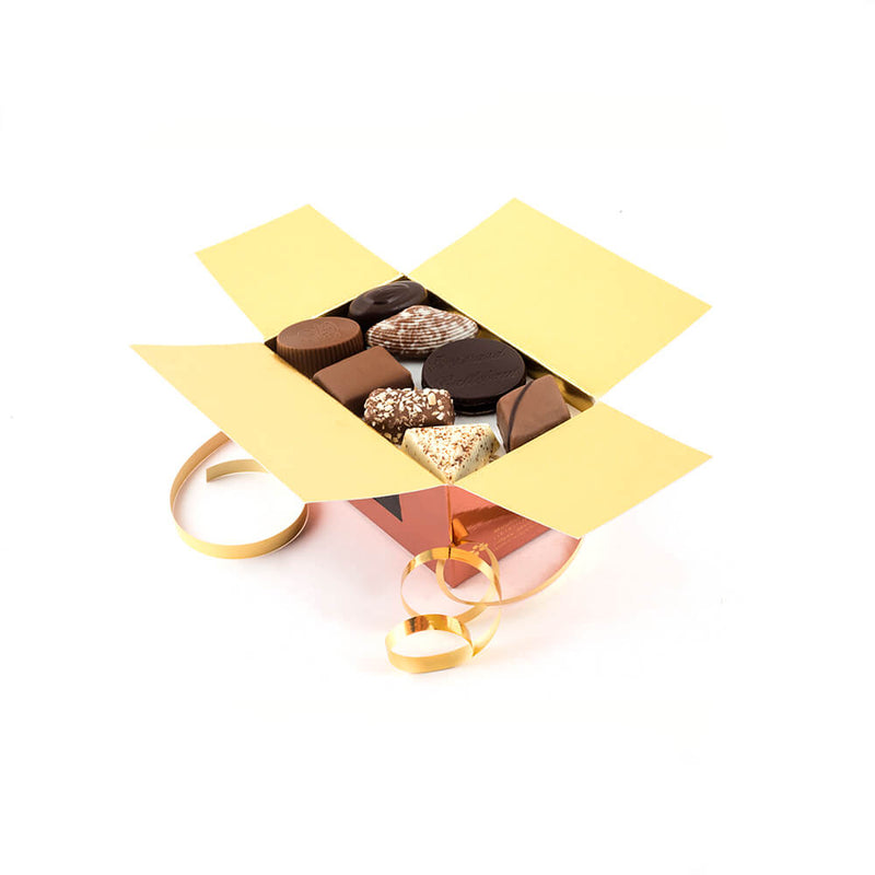 an open Chocolaterie Bernard Callebaut® copper chocolate box with gold ribbon