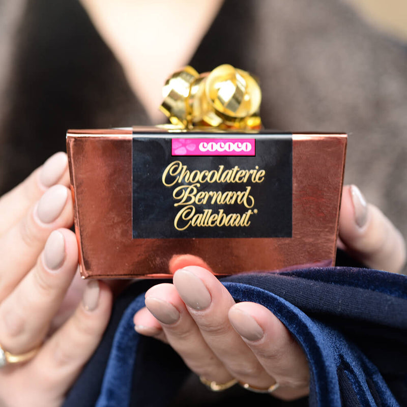 Hands holding Chocolaterie Bernard Callebaut® copper chocolate box with gold ribbon