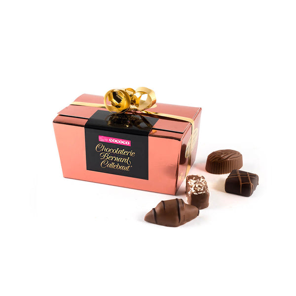 Chocolaterie Bernard Callebaut® copper chocolate box with gold ribbon and four chocolates next to box