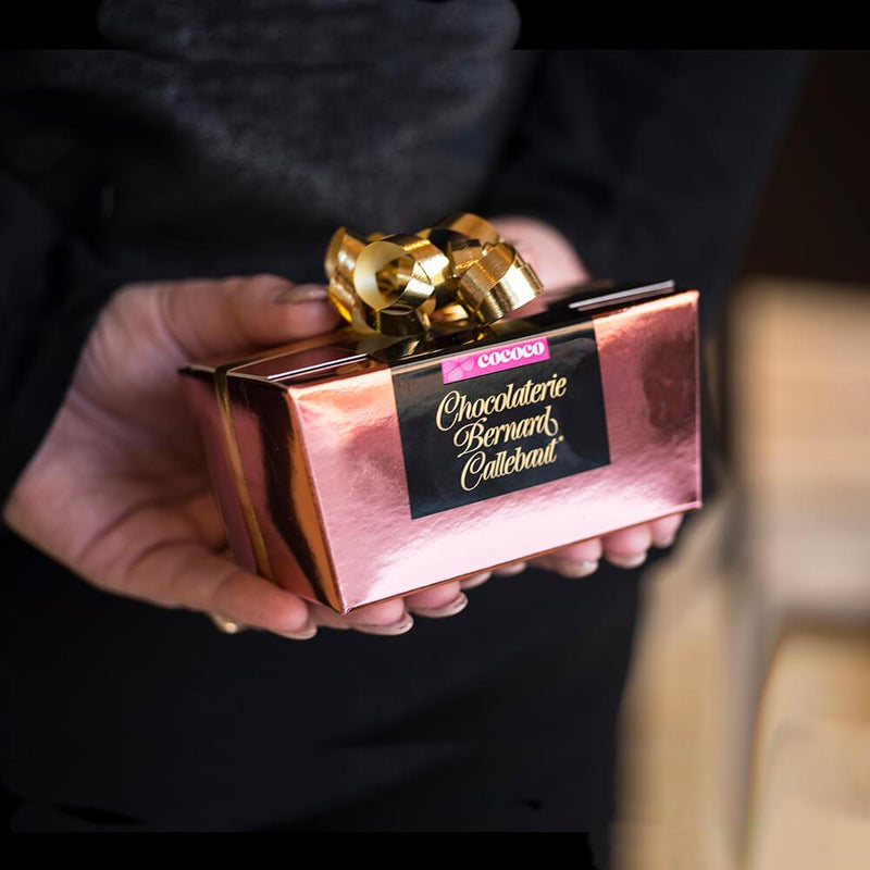 A Chocolaterie Bernard Callebaut® copper chocolate box with gold ribbon held behind someone's back