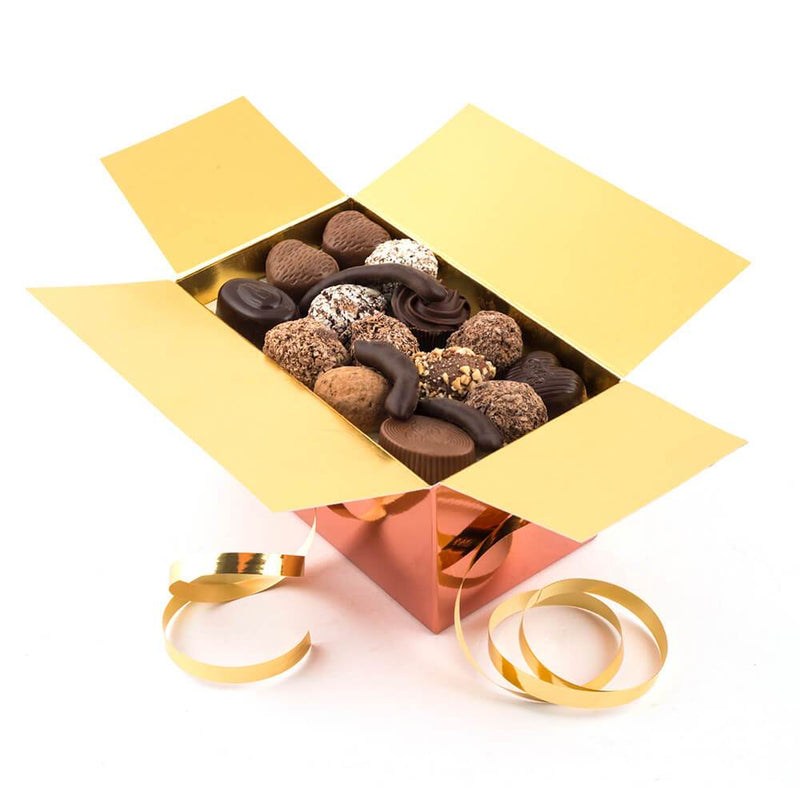 A opened Chocolaterie Bernard Callebaut® copper chocolate box with gold ribbon