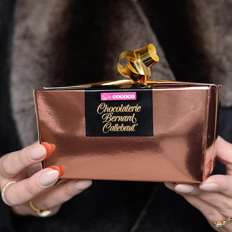 Hands holding a Chocolaterie Bernard Callebaut® copper chocolate box with gold ribbon