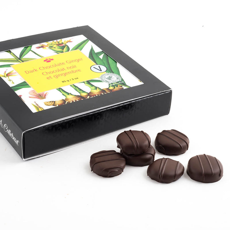 Box of dark chocolate coated candied ginger with 6 chocolate pieces in the foreground