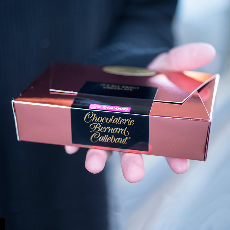 A hand holding a Chocolaterie Bernard Callebaut® copper boxnext to box