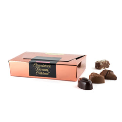 A Chocolaterie Bernard Callebaut® copper box with four assorted chocolates next to box