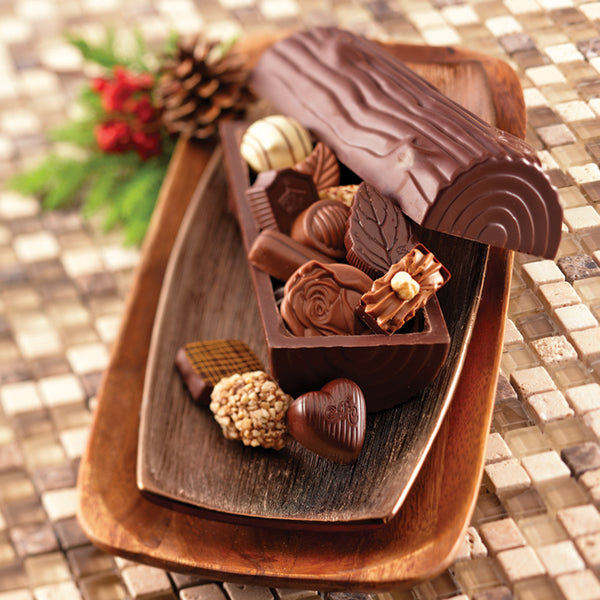 Milk chocolate Yule Log with assorted chocolates on a serving plate