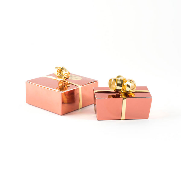 Two copper boxes dressed with shiny curly gold ribbon