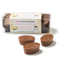A box of four Salted Peanut Butter Chocolates, with three more chocolates in the foreground on a white surface
