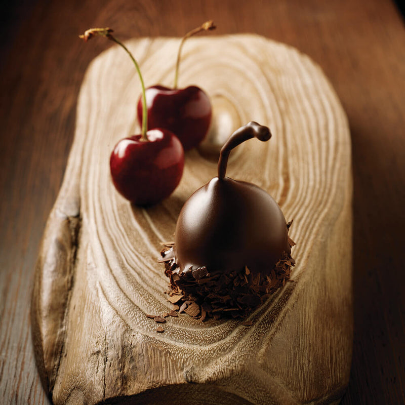 One dark chocolate covered cherry and two fresh cherries sitting on a piece of wood