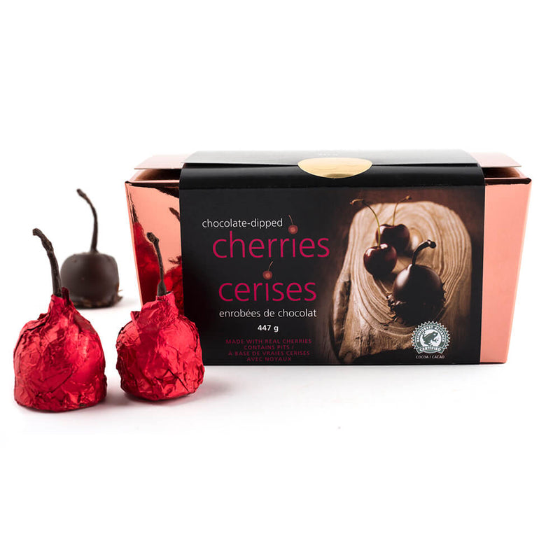Copper box of chocolate dipped marinated cherries with two red foiled cherries next to the box.