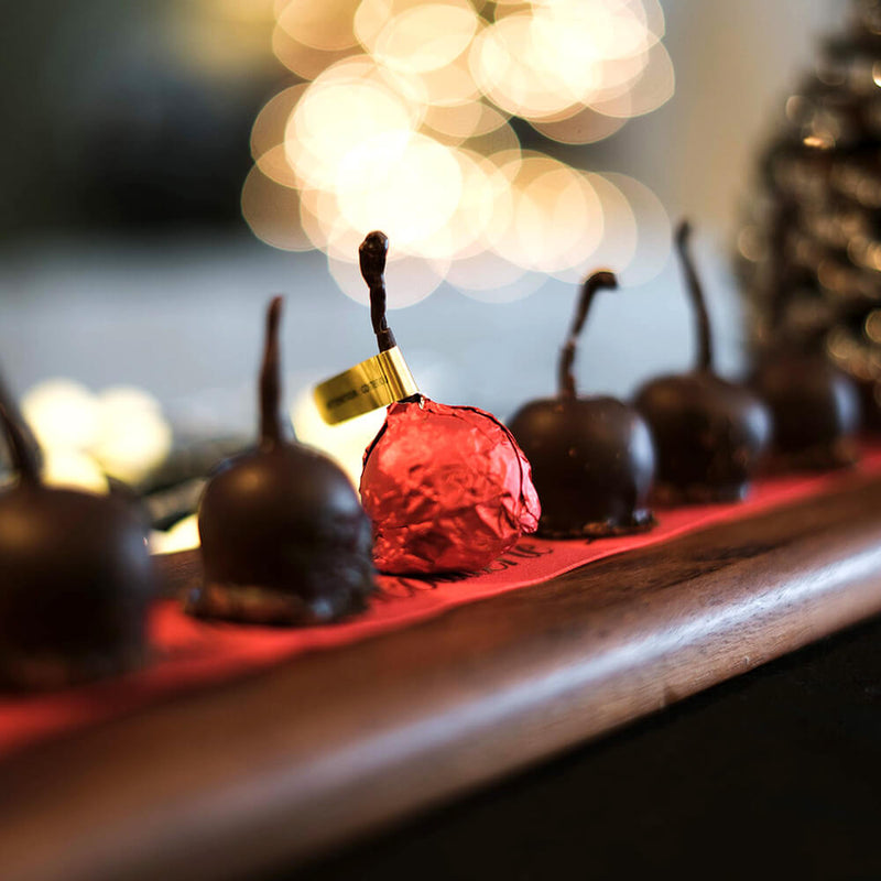 Tray of dark chocolate enrobed cherries with one cherry in the middle wrapped in red foil