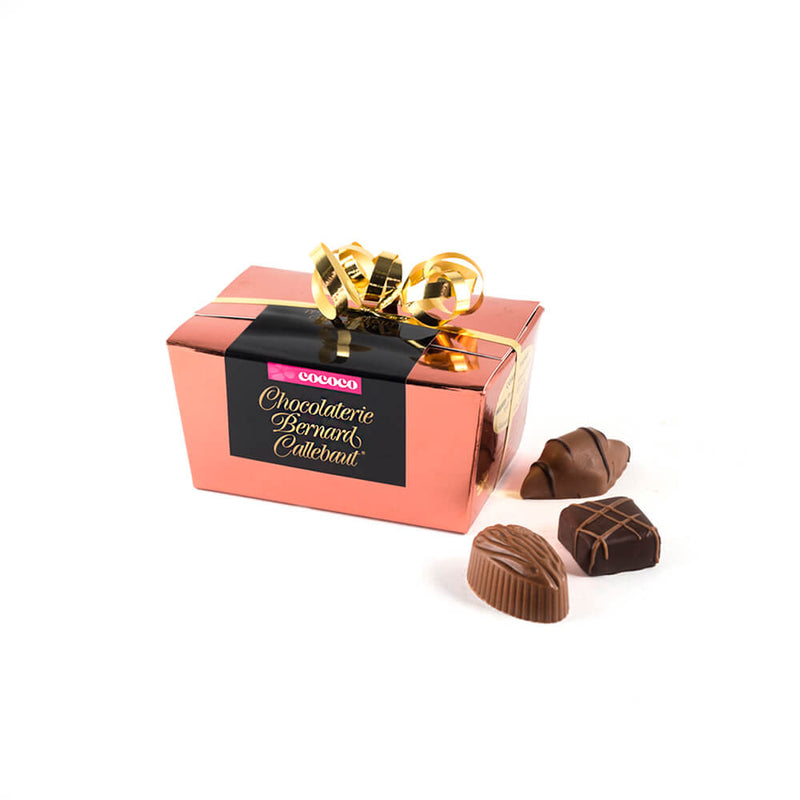 Chocolaterie Bernard Callebaut® copper chocolate box with gold ribbon and three chocolates next to box