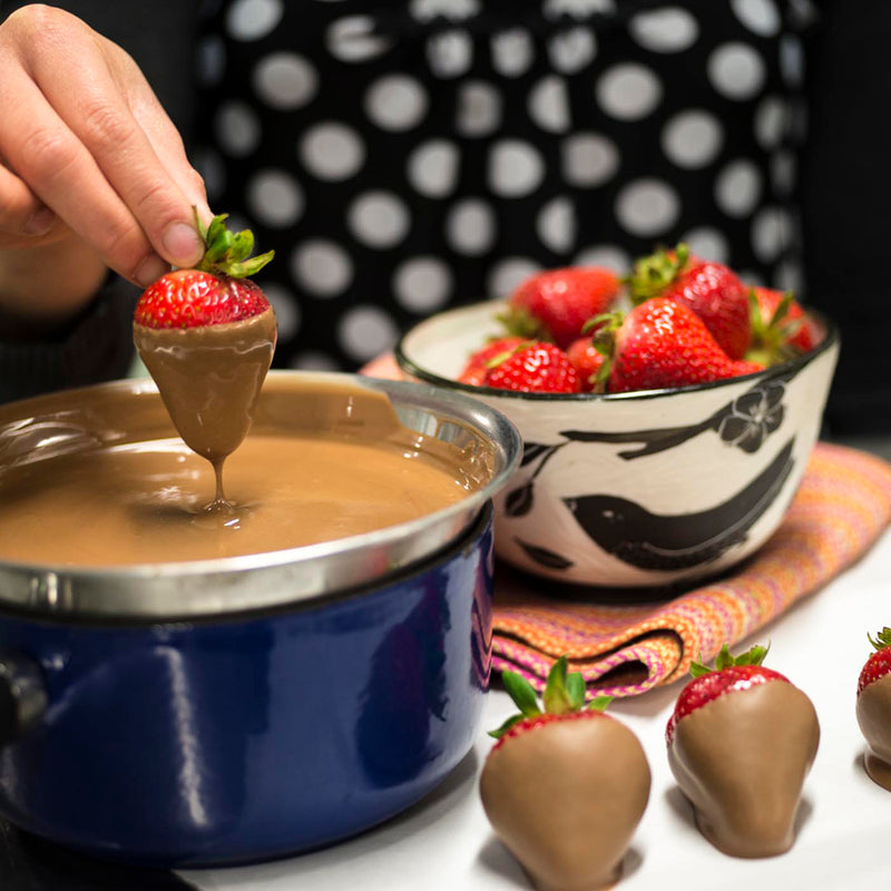 Hand dipping a fresh strawberry into a bowl of milk chocolate. Bowl of strawberries in background.