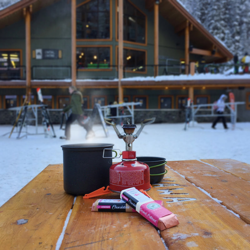 Camping burner with pot outside ski chalet with chocolate bars in forground