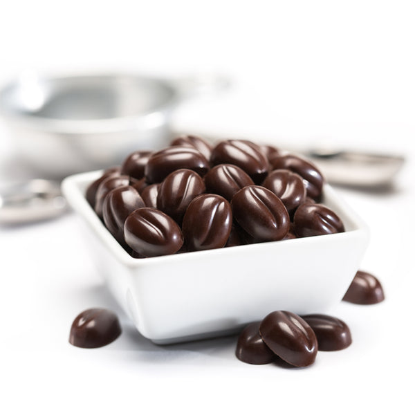 Square white bowl full of dark chocolate morsels, with a few morsels scatters outside of the bowl