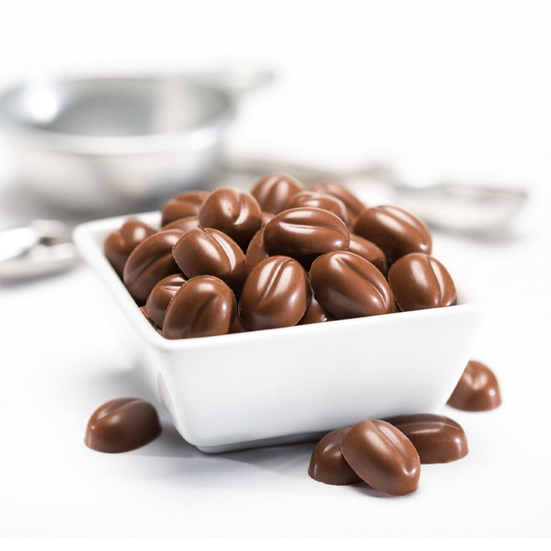 Square white bowl full of milk chocolate morsels, with a few morsels scatters outside of the bowl