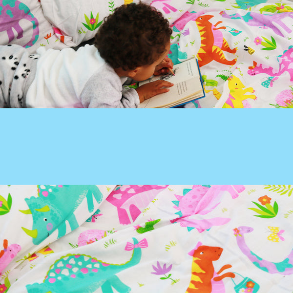 Girl reading a book in her girls pink dinosaur bedding.