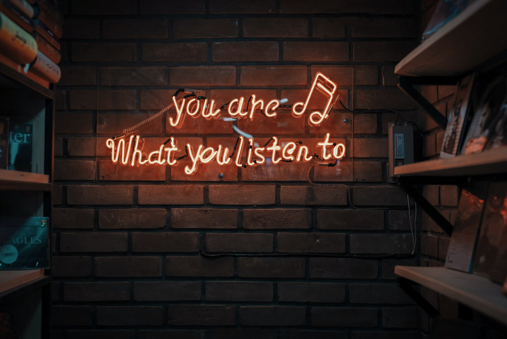 Neon sign saying you are what you listen to. Unsplash.