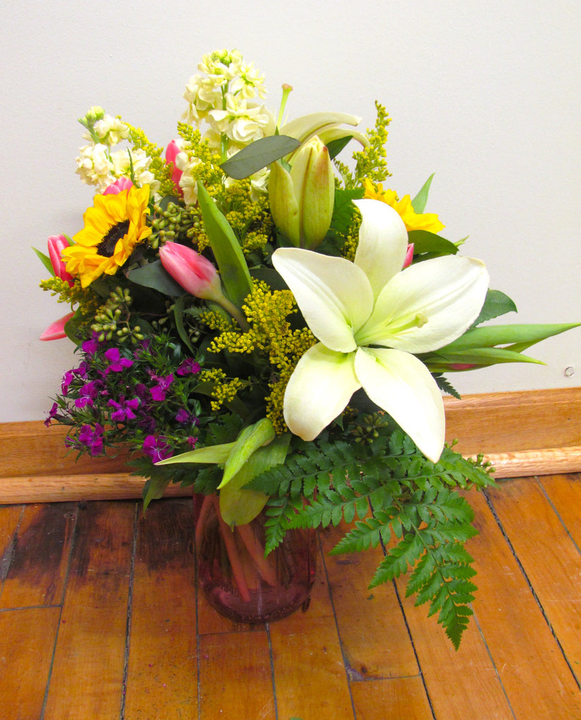 A vase full of beautiful spring flowers like lilies and tulips.