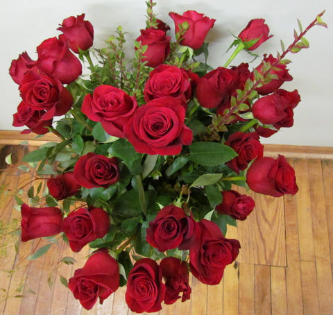 Three dozen red roses with lush greenery