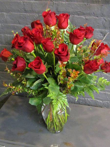 24 roses with greens in a glass vase