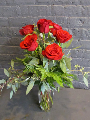 6 red roses with greens in a glass vase