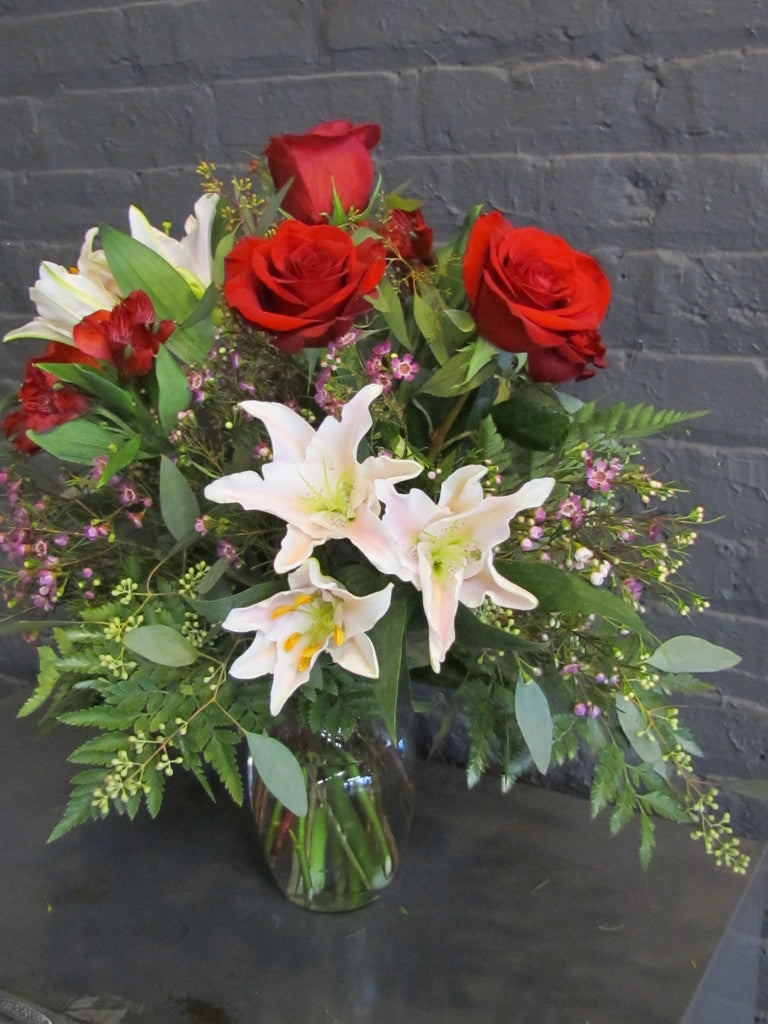 Red roses with lilies and fill in a glass vase