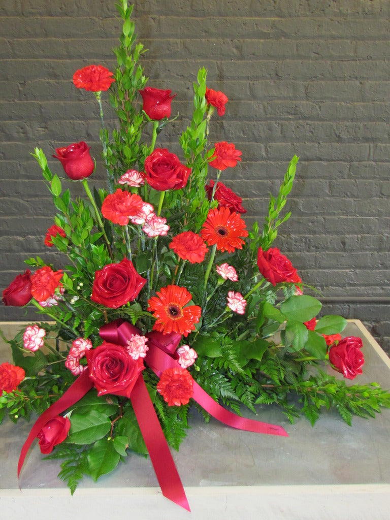 Red, tall, traditional funeral arrangement