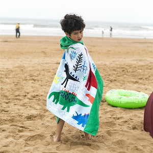 Boy on beach showing kids Hooded Dinosaurs Beach Towel