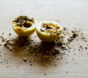 fresh passionfruit spinkled with Thank Fall Mutha Dukkah, a nut seed and spice mix with walnuts, roasted nuts, coconut, cinnamon, nutmeg. Crunchy everyday-gourmet, plant-based seasoning sprinkled on meals.