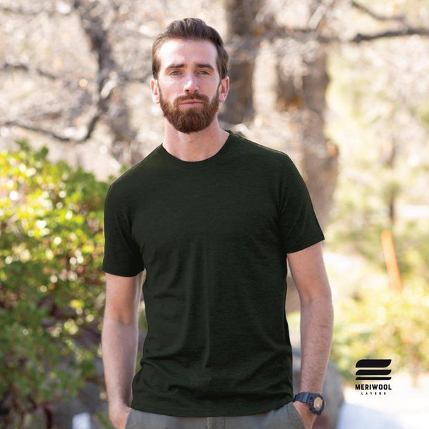 man standing outside wearing an army green merino wool base layer shirt