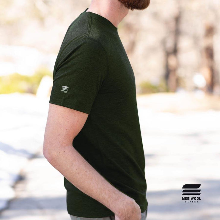 side profile man wearing an army green merino wool 190g lightweight t shirt outside