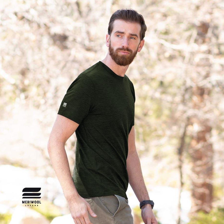 man walking outside wearing an army green merino wool 190g lightweight tee