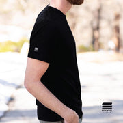side profile man wearing a black merino wool 190g lightweight tee outside