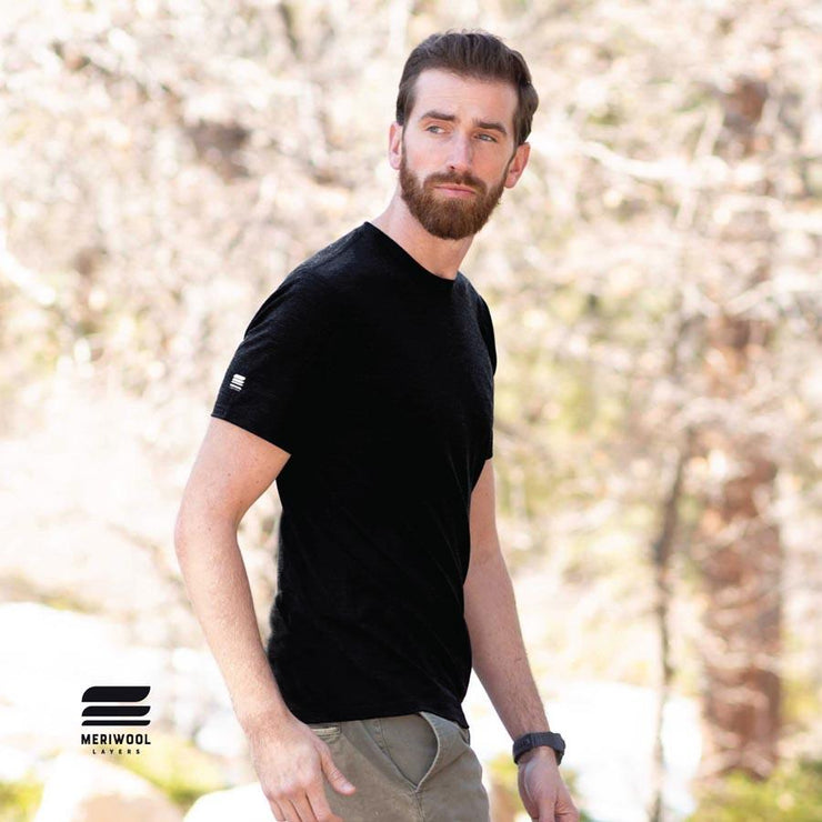 man walking outside wearing a black merino wool 190g lightweight t shirt
