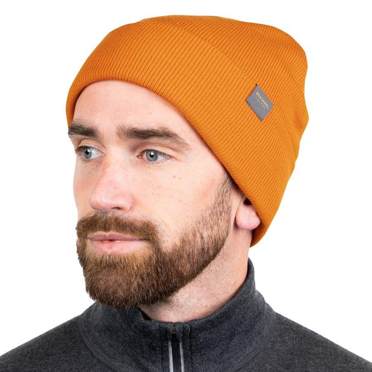 man wearing a orange merino wool ribbed knit beanie