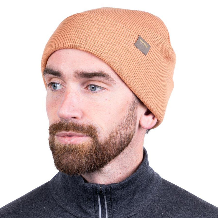 man wearing a peach colored merino wool ribbed knit beanie