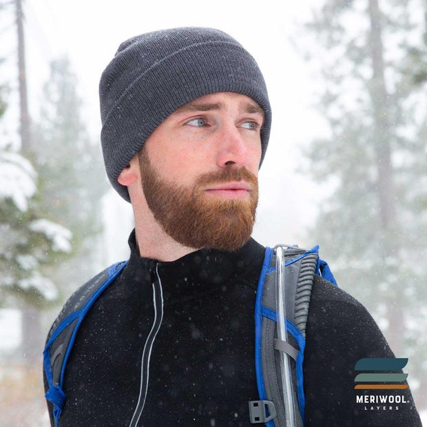 man walking in the snow wearing a gray merino wool beanie and base layers
