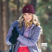 woman in the snow with a snow board wearing a wine colored merino wool beanie