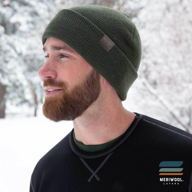 man outside in the snow wearing a army green merino wool beanie and base layers