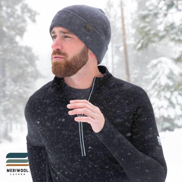 man running in the snow wearing a gray merino wool ribbed knit beanie