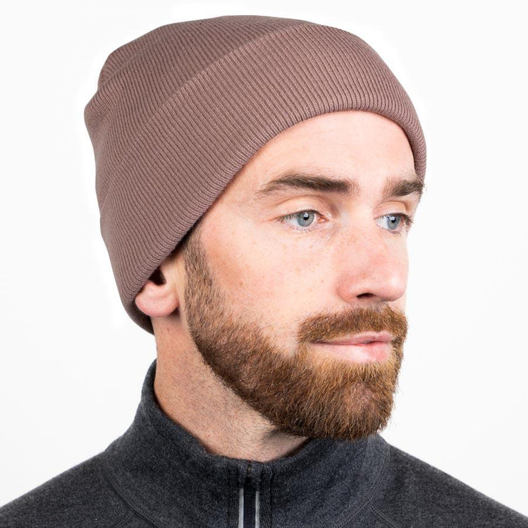 man wearing a rose colored merino wool ribbed knit beanie